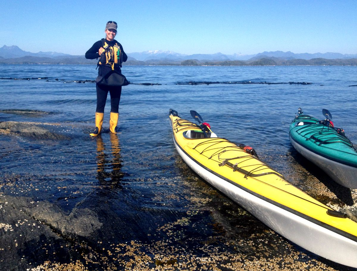 Kayak Guide wearing rubber boots in the shallow tides by her kayak